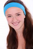 Smiling fitness girl with blue hairband over white background