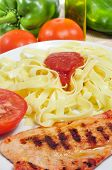 closeup of a combo platter with tagliatelle with tomato sauce and grilled chicken