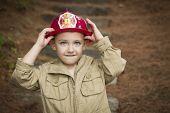 Happy Adorable Child Boy with Fireman Hat Playing Outside.