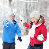 Winter fun - couple in snowball fight having fun together in forest snow landscape. Happy young inte