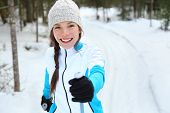 Cross-country skiing woman doing classic nordic cross country skiing in trail tracks in snow covered