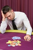 Man leaning on poker table looking disappointed in casino