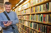 stock photo of librarian  - Man smiling while holding tablet pc in the library - JPG