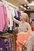 stock photo of take off clothes  - Woman taking clothes off the clothes rack - JPG