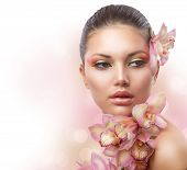 Beautiful Girl With Orchid Flowers.Beauty Woman Face. Perfect Skin. Professional Make-up.Makeup