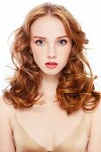 Portrait of young beautiful girl with curly red hair on white background