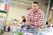 pic of cart  - man with shopping cart with food produces in supermarket - JPG