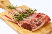 Rack of lamb with rosemary on a wooden board.