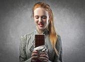 Blonde girl eating a chocolate bar