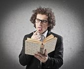 stock photo of finger-licking  - Professor licking a finger to turn the page of a book - JPG