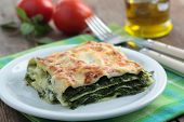 Lasagna with spinach on a rustic table