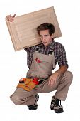 portrait of young cabinetmaker carrying cupboard door over shoulder
