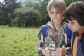 Two young boys with backpacks using compass