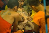 NAKHON CHAI, THAILAND - MAR 23: Unidentified monk makes traditional Yantra tattooing during Wai Kroo