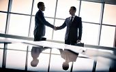 stock photo of trust  - Silhouettes of two businessmen standing by the window and handshaking - JPG