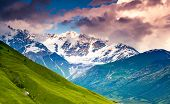 Majestic colorful sunset at the foot of  Mt. Shkhara. Dramatic sky. Upper Svaneti, Georgia, Europe. Caucasus mountains. Beauty world.