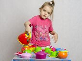 Girl pours a Cup of water from the teapot playing child kitchen utensils