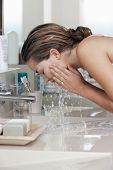 Closeup of beautiful young woman washing face in bathroom