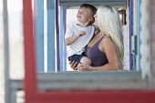 Blond young woman carrying son at porch