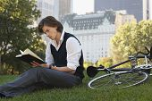 Handsome young businessman reading book by bicycle in park