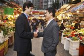 Side view of young businessmen shaking hands at street market
