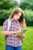 Outdoor Portrait Of A Beautiful Teenager Girl In Casual Clothes With Backpack Holding Digital Tablet