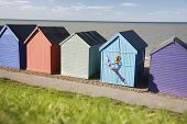 picture of herne bay beach  - Full length of young woman jumping in front of huts at beach during summer - JPG