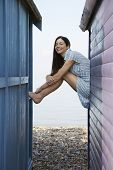 stock photo of herne bay beach  - Side view portrait of happy young woman sitting on balustrade of beach house - JPG