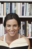 Closeup portrait of happy young woman with book against shelves at home