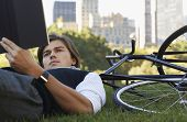 Young businessman lying down on bicycle while reading book in park