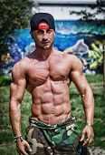 Shirtless Bodybuilder Showing Torso Muscles, Abs, Pecs And Arms Outdoors