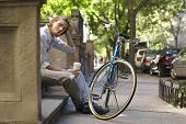 Portrait of happy young businessman holding disposable coffee cup while sitting on steps in front of bicycle