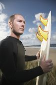 Side view of male surfer carrying surfboard on beach looking away