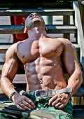 Muscular Bodybuilder Laying On Wood Stairs In The Sun