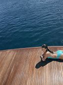 High angle view of sensuous woman in swimsuit relaxing on yacht's floorboard