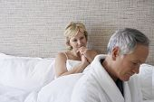 Unhappy middle aged couple in bedroom