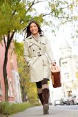 Young stylish female professional holding handbag wearing modern trench coat walking in urban city s