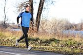 stock photo of fall day  - Male runner man running in autumn on cold day wearing long tights and long sporty jogging outfit - JPG