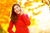 stock photo of foliage  - Smart phone Autumn woman talking on mobile phone in fall - JPG