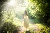 stock photo of fantasy  - Beautiful young woman wearing elegant white dress walking on a forest path with rays of sunlight beaming through the leaves of the trees - JPG