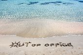 Out Of Office Written On Sand On A Beautiful Beach, Blue Waves In Background