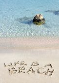 Life Is A Beach Message Written On White Sand, With Tropical Sea Waves In Background