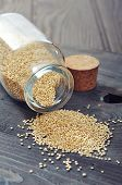 picture of quinoa  - Raw quinoa seeds in the glass bottle on wooden background closeup - JPG