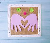 Wooden frame with paper arms and colorful buttons on wooden background