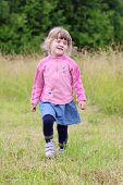 Little Beautiful Girl In Skirt Going And Hamming At Green Meadow In Summer Day