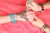 Process of applying Mehndi on female hand on color cloth background