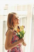 Beautiful Smiling Woman Tulips Stands Near Big Window In Sunlight And Looks Up