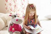 Pretty Little Blonde Girl Sits Near Soft Toy On Carpet And Reads Book