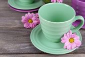 Cups and saucers with flowers on wooden background