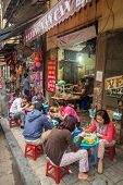 HANOI, VIETNAM - APRIL 8, 2014: Customers have their meal on the street stall on April 8, 2014 on Ha